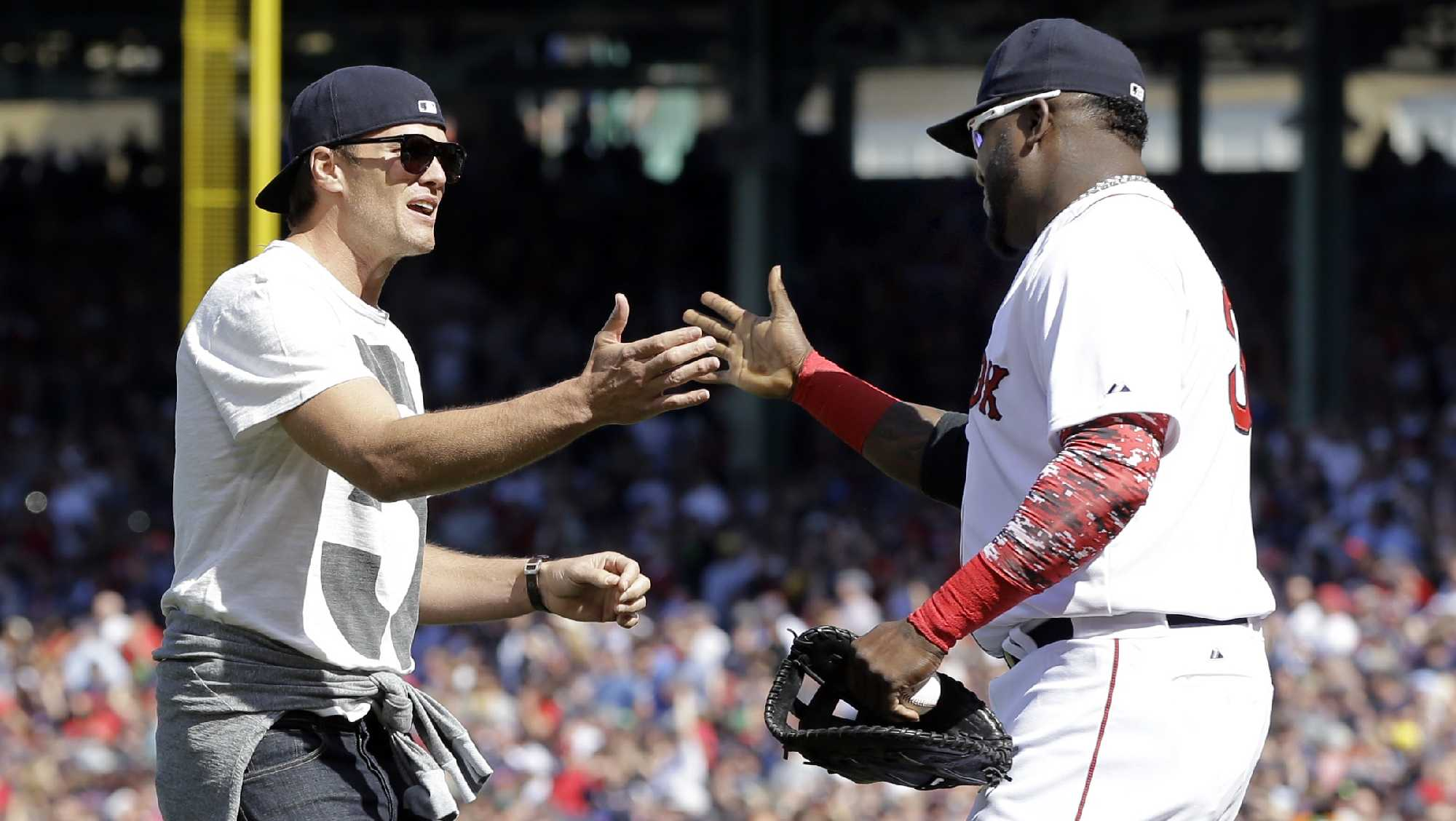 New England Patriots quarterback Tom Brady, left, greets Boston Red Sox's David Ortiz after throwing the ceremonial first pitch prior to the home opener baseball game between the Boston Red Sox and the Washington Nationals at Fenway Park in Boston, Monday, April 13, 2015.