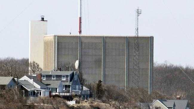 In this 2011 file photo, a portion of the Pilgrim Nuclear Power Station sits beyond houses along the coast of Cape Cod Bay in Plymouth. Entergy Corp., owner of the power plant which went online in 1972, announced Tuesday it will close the plant by June 2019.