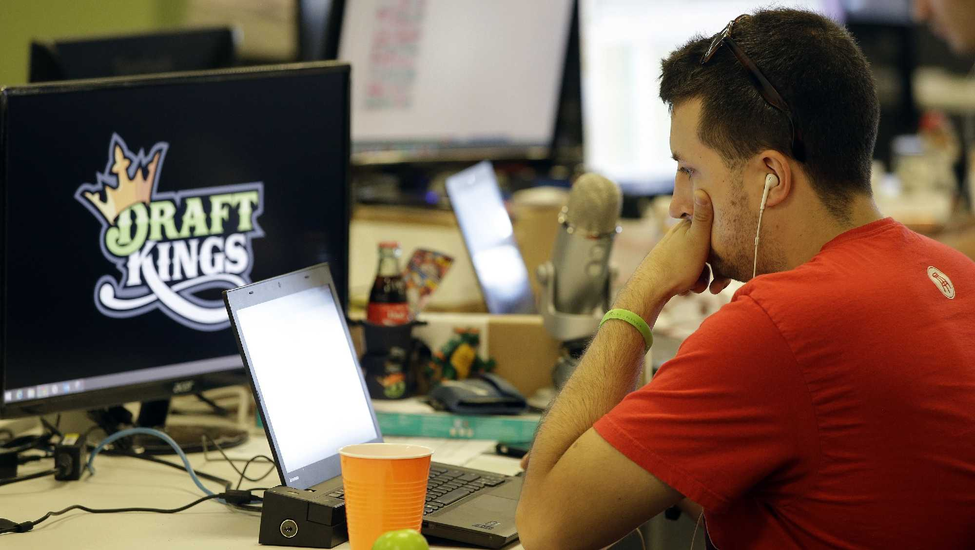 In this Sept. 9, 2015, file photo, Devlin D'Zmura, a trending news manager at DraftKings, a daily fantasy sports company, works on his laptop at the company's offices in Boston.