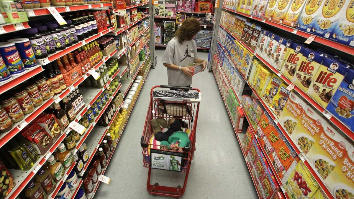 FILE - In this Dec. 14, 2010, file photo, Alicia Ortiz shops through the cereal aisle as her daughter Aaliyah Garcia catches a short nap in the shopping cart at a Family Dollar store in Waco, Texas. Up and down supermarket aisles, rows of perfectly placed products reflect calculated deliberations aimed at getting shoppers to spend more. Take cereal, for example. Research published in the Journal of Environment and Behavior found that kids' cereals tended to be placed on lower shelves where they are more eye-level with children. It's just one example of the tactics food companies and supermarkets use to sway what people put in their carts.