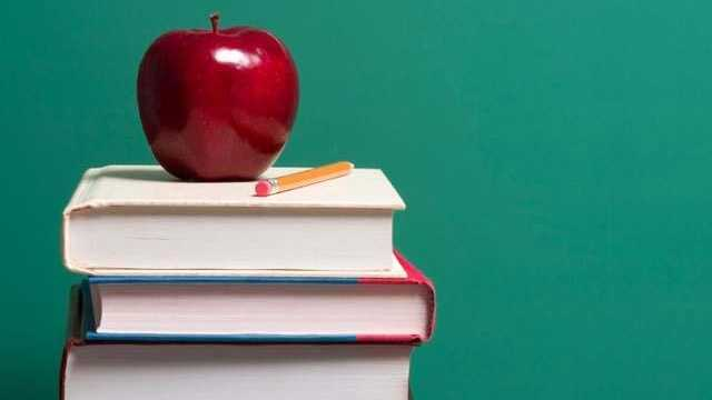 Apple on top of school books