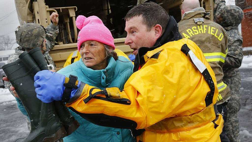 Marshfield police detective Greg Davis helps Robin Dunn of Brant Rock to safety after she was rescued from her home on Jan. 4, 2018. Greg Derr/The Patriot Ledger